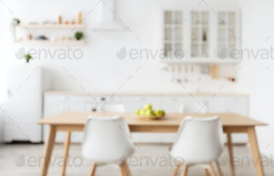 Blurred background of light kitchen interior in scandinavian style with wooden dining table, copy