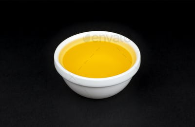 Vegetable oil in white bowl on black background