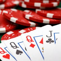 Red playing chips and cards on poker table