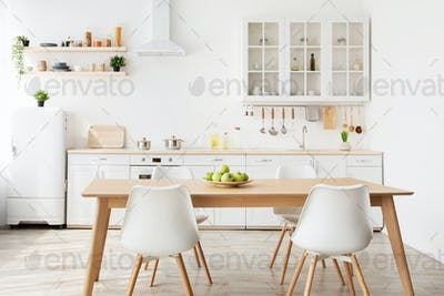 Minimalist scandinavian style. Dining room and light kitchen design with wooden table and white