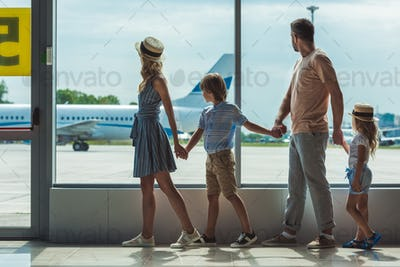 side view of parents and little kids looking out window together in airport