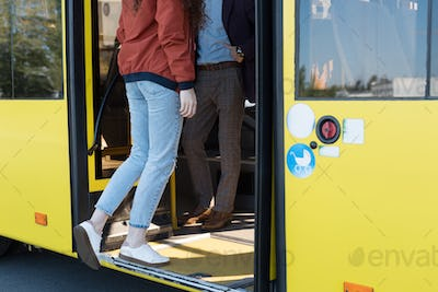 cropped shot of woman in casual clothing entering city bus
