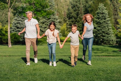 happy grandchildren and grandparents holding hands while running on meadow