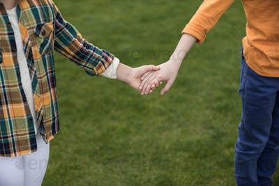 Cropped shot of two little children holding hands while standing on green grass