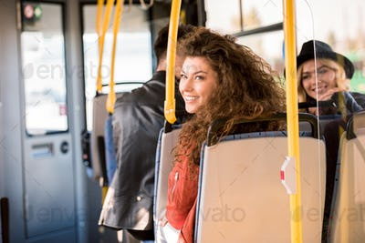 beautiful smiling young women sitting together in city bus