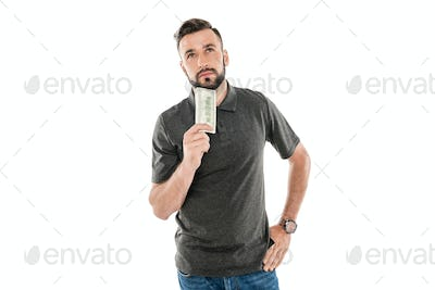 portrait of pensive man with dollar banknote in hand isolated on white