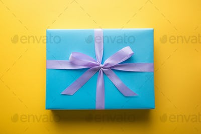 top view of blue gift box with violet ribbon on yellow background