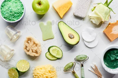 top view of natural beauty products and gadgets near fresh fruits and vegetables on marble surface