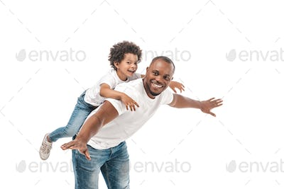 happy african american man piggybacking adorable son and imitating flying on white background