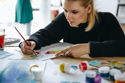 cropped shot of focused young fashion designer drawing sketch at workplace