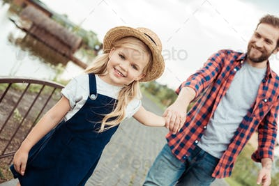 selective focus of father and little daughter holding hands while walking in park together