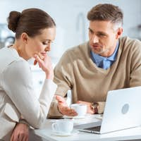 adult couple using laptop and having conversation during breakfast in morning