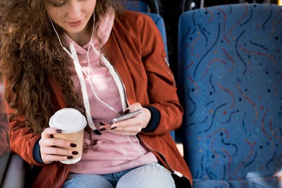 beautiful smiling girl in earphones using smartphone and drinking coffee in bus