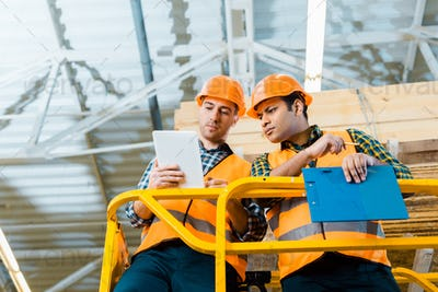 thoughtful multicultural workers using digital tablet while standing on scissor lift in warehouse