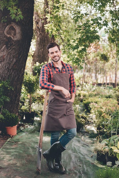 smiling gardener in apron and rubber boots leaning on spade while standing in garden