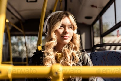 portrait of young thoughtful woman listening music in headphones while riding in public transport