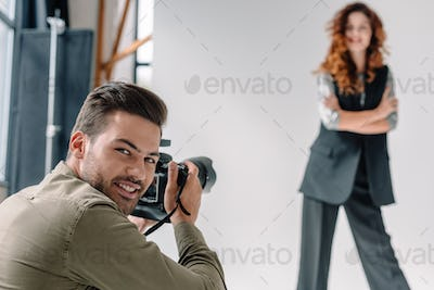 professional photographer and attractive model on fashion shoot in photo studio with lighting
