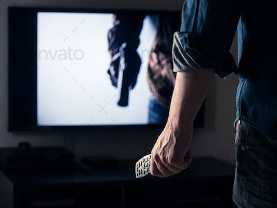 Man holding a tv remote control while watching an action movie