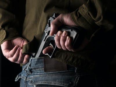Man hiding a gun behind his back