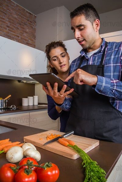 Couple in home kitchen looking recipe with a electronic tablet