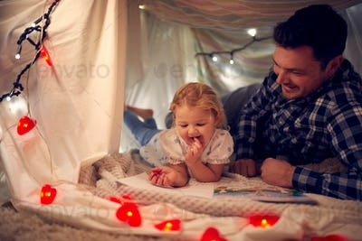 Father And Young Daughter Drawing Picture In Homemade Camp In Child's Bedroom At Home