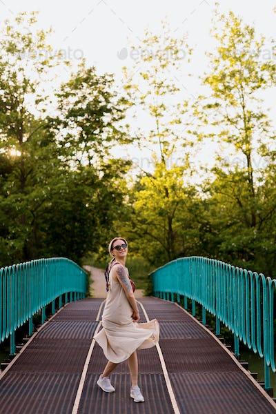 Carefree woman in a dress walking on the bridge