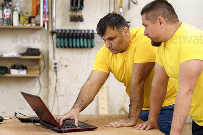 Carpenters using laptop in workshop, searching for a solution