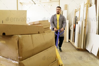 Man carry furniture cardboard boxes in their workshop
