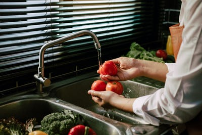 Asian hands woman washing vegetables tomato and preparation healthy food in kitchen.
