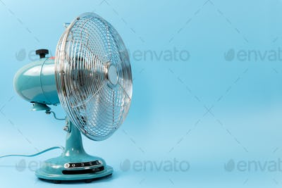 Vintage tabletop fan isolated on a blue background