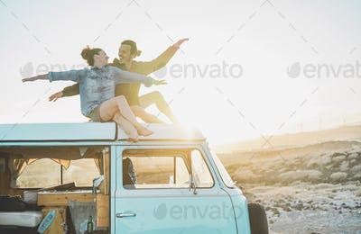 Happy couple sitting on top of minivan roof at sunset