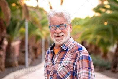Portrait of attractive senior man white-hair and beard looking at camera. Standing outdoor
