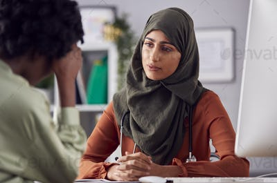 Female Doctor Or Consultant Wearing Headscarf Having Meeting With Unhappy Female Patient