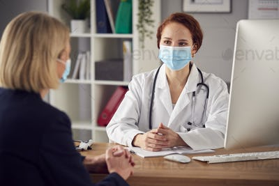 Female Doctor In White Coat Wearing Face Mask Having Meeting With Mature Woman Patient In Office