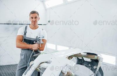 With painting gun. Caucasian automobile repairman in uniform works in garage