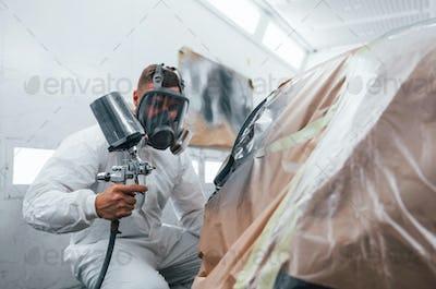 Painting job in progress. Caucasian automobile repairman in uniform works in garage
