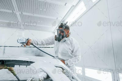In protective mask. Painting the car. Caucasian automobile repairman in uniform works in garage