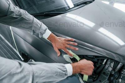 Detailed work. Caucasian automobile repairman in uniform have job in garage