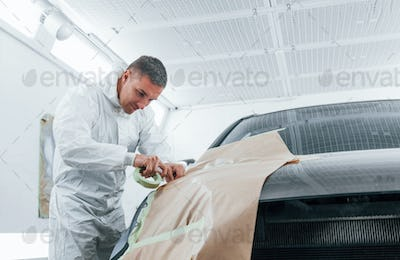 Covering car by brown cloth. Caucasian automobile repairman in uniform works in garage