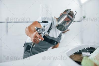 Uses painting gun. Caucasian automobile repairman in uniform works in garage
