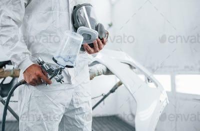 Close up view. Caucasian automobile repairman in uniform works in garage