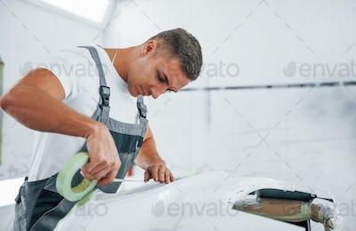 Works with car hood. Caucasian automobile repairman in uniform in garage