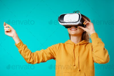 Young smiling casual woman wearing VR glasses