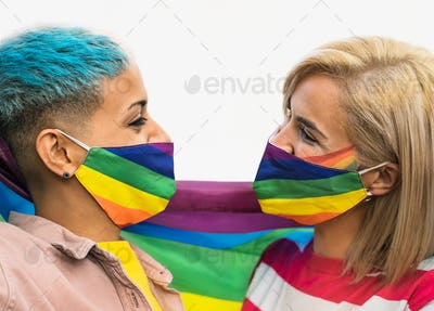Happy gay couple wearing face mask celebrating gay pride event during corona virus pandemic