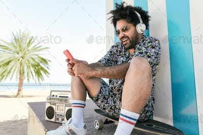 Latin man using mobile phone and listening music with headphones and boombox stereo on beach