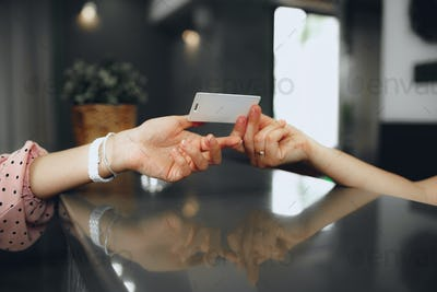 Hotel receptionist giving key-card to a client at front desk