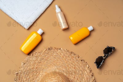 Suntan cosmetic product with towel, hat and sunglasses