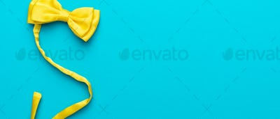 Top View Photo Of Yellow Bow Tie Over Turquoise Blue Background With Copy Space