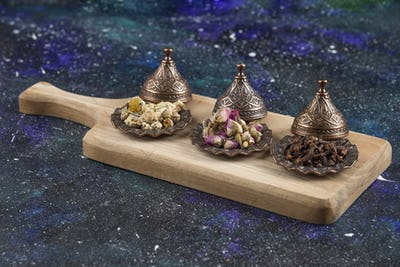 Different herbs and spices on wooden board
