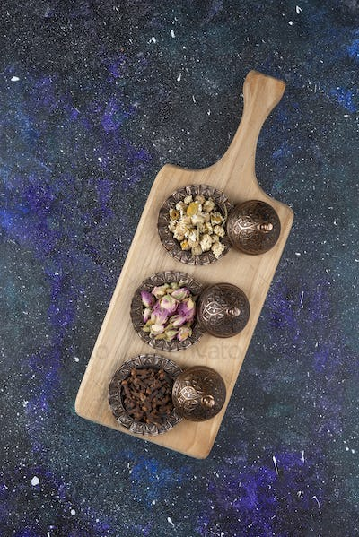 Top view of Different herbs and spices on wooden cutting board